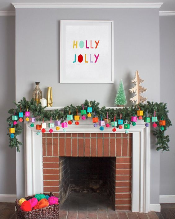 an advent calendar made of colorful boxes and pompoms hanging ona  lush evergreen garland