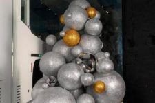 24 an oversized Christmas tree composed of oversized silver and gold glitter Christmas ornaments or balls will make a statement