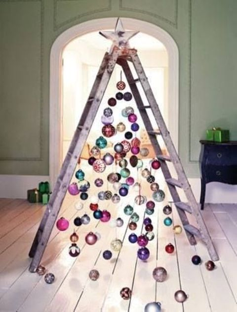 a chic ladder christmas tree with colorful ornaments all over and on the floor for a messy and relaxed touch