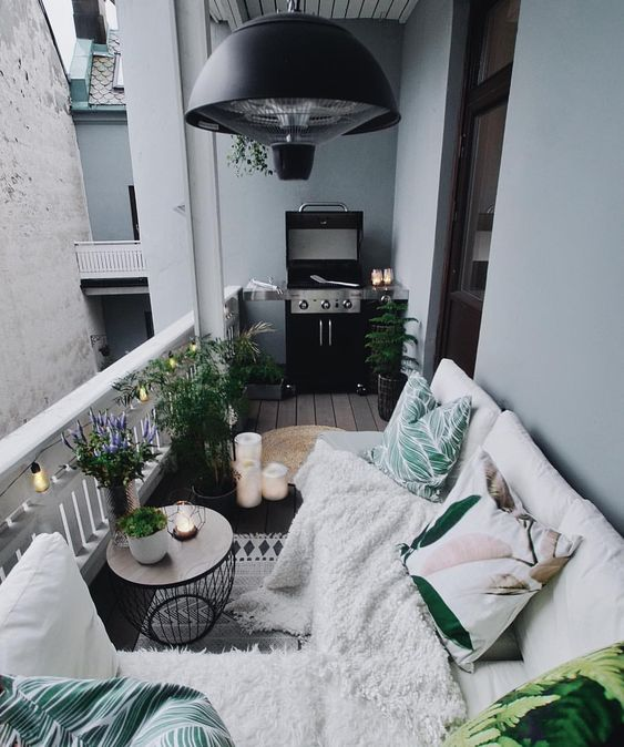 a cozy Nordic balcony with potted plants, printed textiles and a grill - all you need in one