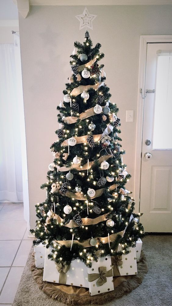 a rustic glam Christmas tree with white and silver ornaments, pinecones, icicle ornaments and lights