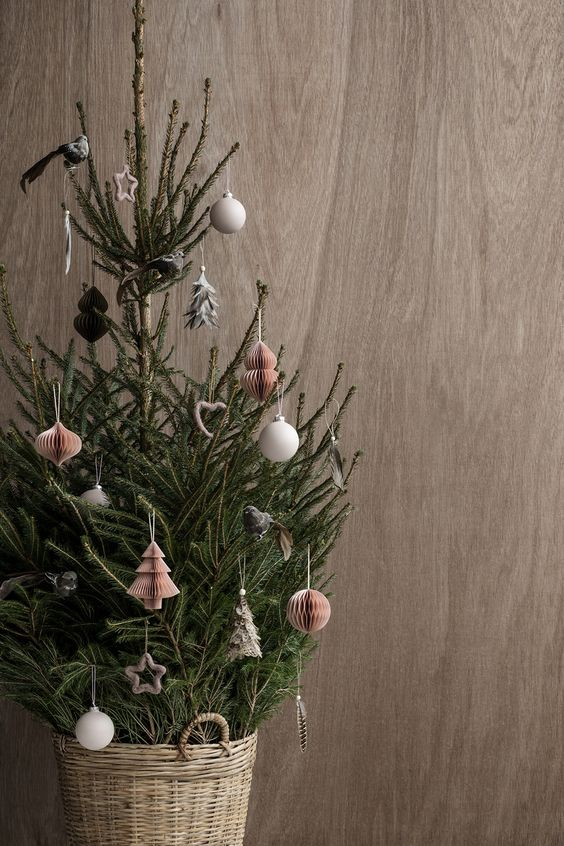 a small tree decorated with white ball ornaments and red paper ones and placed in a basket for a Nordic feel
