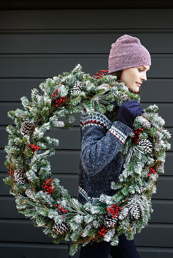 a snowy evergreen wreath with snowy pinecones and fake berries feels very holiday like and can be easily DIYed