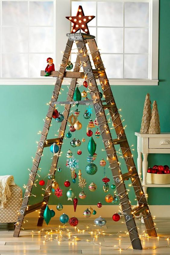 a fun Christmas tree of a laddder and colorful ornaments plus lights and a shiny star on top