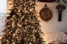 26 a rustic luxe Christmas tree with snowy and gilded pinecones, burlap ribbons, large metal ornaments and lots of lights