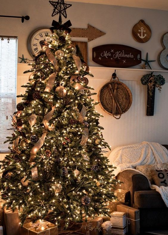 a rustic luxe Christmas tree with snowy and gilded pinecones, burlap ribbons, large metal ornaments and lots of lights