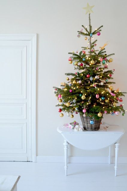 a small tree in a basket styled with super colorful ornaments and lights plus a star on top