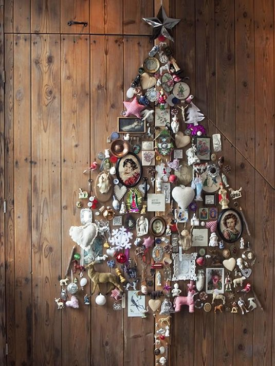 a whimsical wall-mounted Christmas tree of figurines, frames, photos and various vintage stuff for a shabby chic space