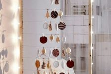 27 take a large frame, hang some yarn and form a Christmas tree of your favorite ornaments, line it up with lights