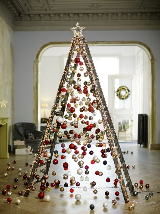take a usual ladder and cover it with lights, then attach Christmas ornaments on various heights to form a creative tree