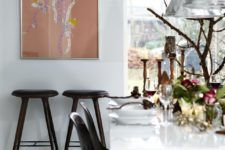 02 The dining space is accented with black chairs, candles, florals and catchy pendant lamps