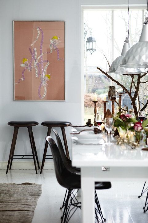 The dining space is accented with black chairs, candles, florals and catchy pendant lamps