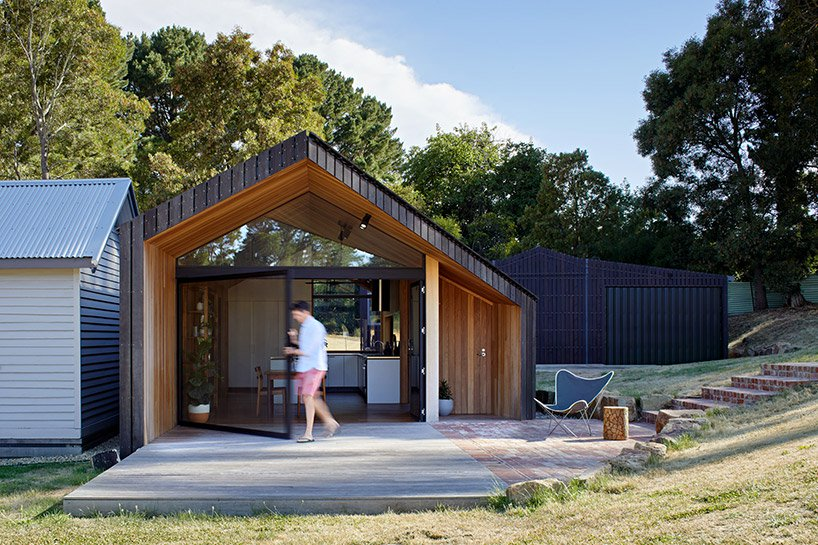 The house features a creative geometric shape and an outdoor deck in front of the house to enjoy fresh air