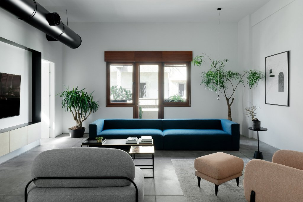 The living room is done with a stylized metal pipe, neutral coomfy furniture and a bold blue sofa
