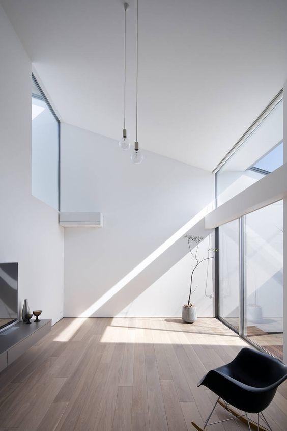 a minimalist space with an attic roof, much natural light coing through glazings and a minimum of furniture