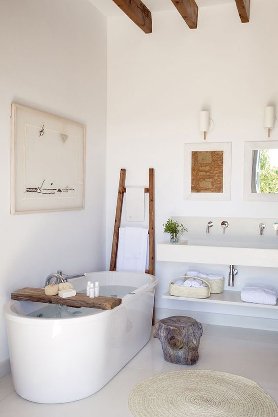 a neutral bathroom with wooden touches and a free-standing bathtub plus some rough wood accessories