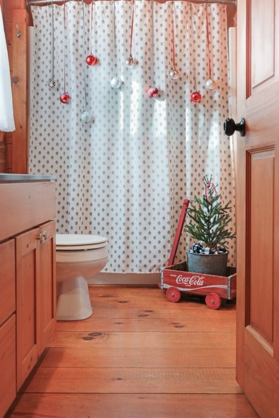 avoid using floor space as there isn't much in a bathroom, hang ornaments on the shower curtain for a festive feel