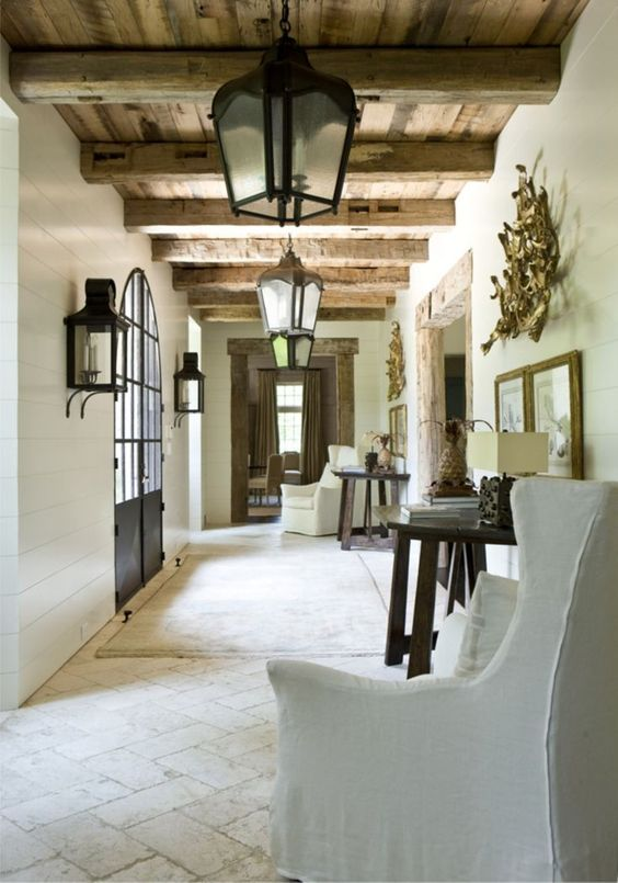white wooden walls, a tiled floor, a wooden ceiling and beams make up a vintage Mediterranean space