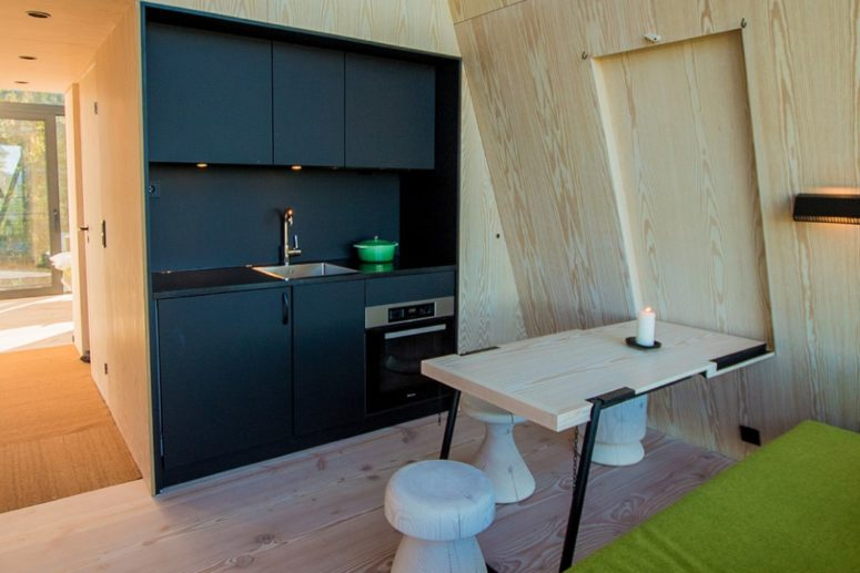 The main space is a dining-living-kitchen one, with black cabinets, a comfy table and stools and a bright upholstered bench