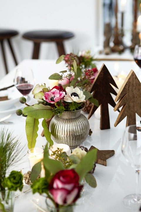 The table is decorated with wooden trees and floral centerpieces in traditional Christmas colors