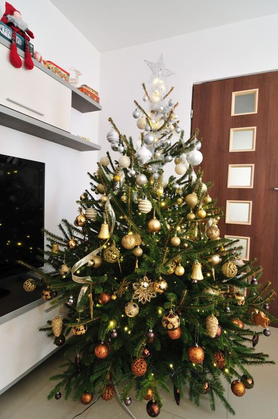 a beautiful and luxurious ombre silver to gold and copper Christmas tree with lights and a star on top looks very chic