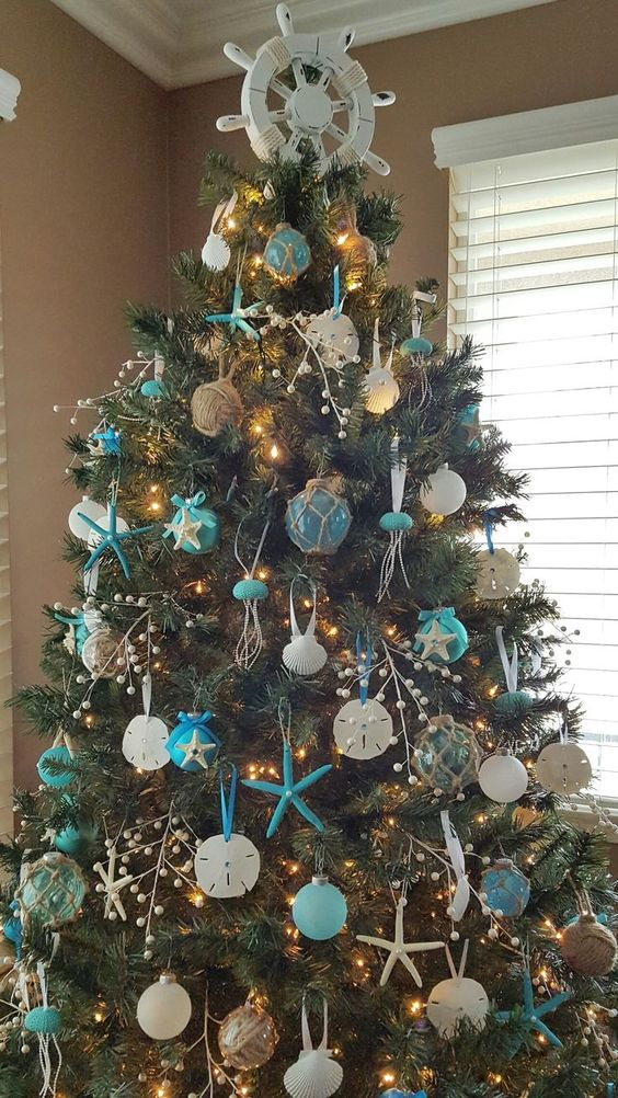 a bold beach Christmas tree with blue and white ornaments styled as floats and shells plus twine balls