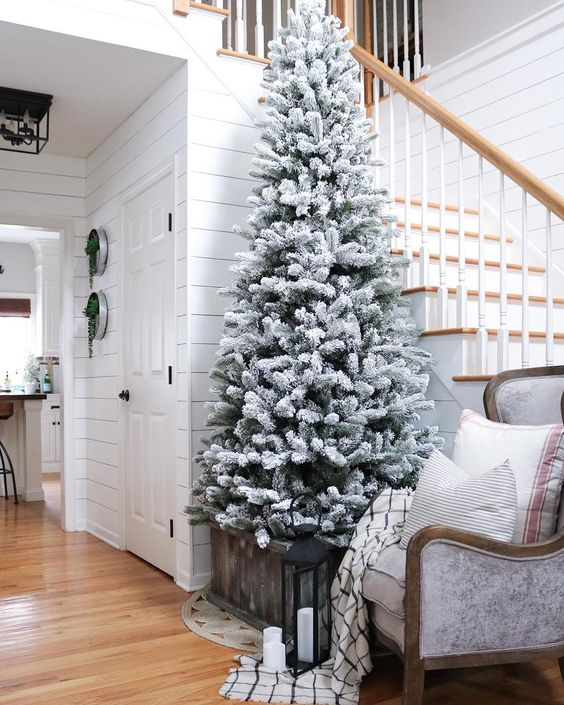 a flocked Christmas tree with no decor in a crate is a great idea for any entryway, add some candles around