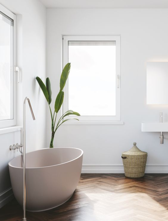a peaceful bathing space with a free-standing blush bathtub looks very relaxing and comfortable