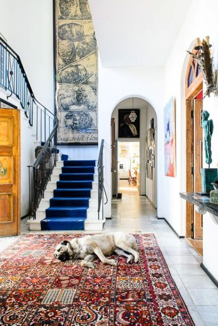 a very eclectic entryway with an oversized vintage artwork balanced with a large boho chic rug