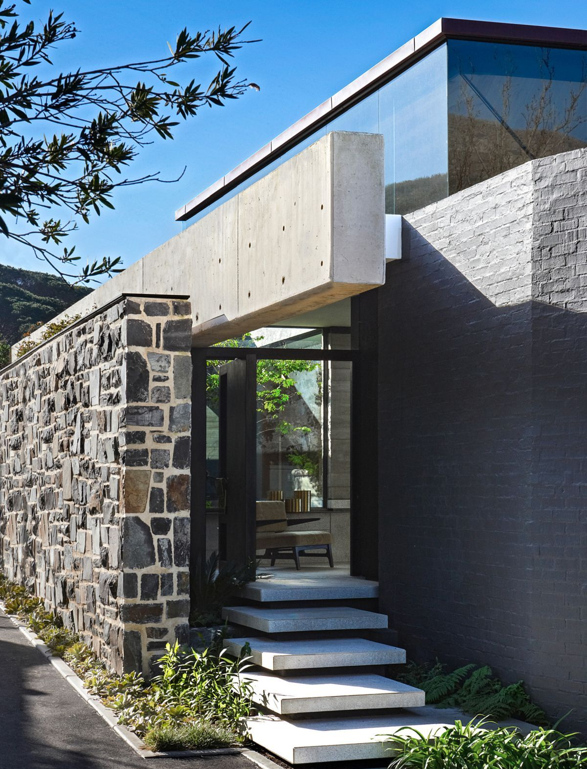 A stone wall hides the lower floors from the street making them private