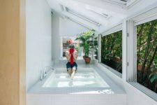 04 The bathtub is a large pool-like space clad with white tiles, with skylights and windows that show off greenery walls