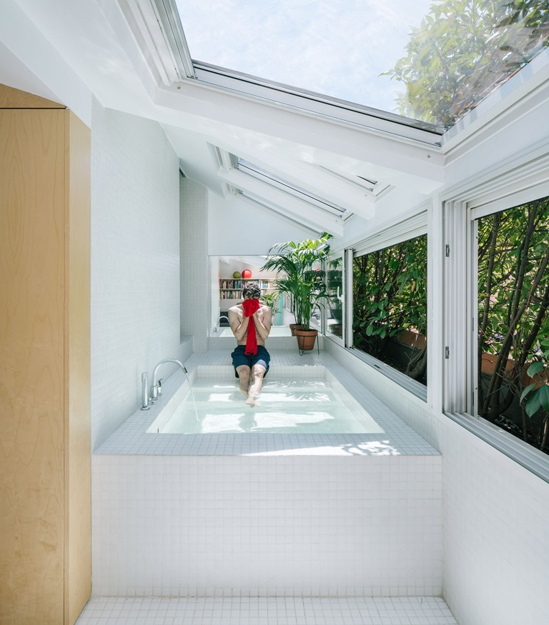 The bathtub is a large pool-like space clad with white tiles, with skylights and windows that show off greenery walls