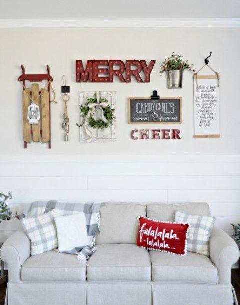 a cozy gallery wall with marquee lights, signs, a wreath, a lantern, a sleigh and some greenery