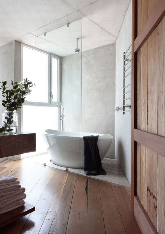 a modern rustic bathroom with a free standing sculptural bathtub and large yet frosty glass windows for natural light