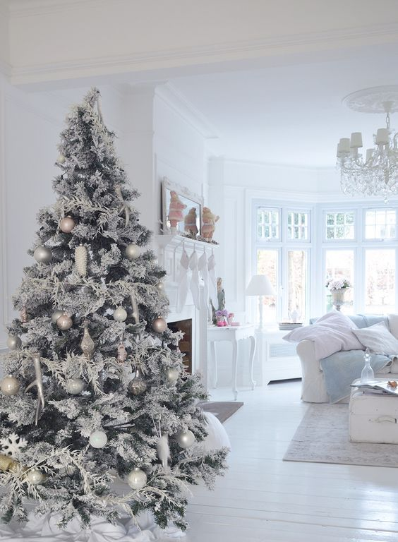 a snowy white and silver Christmas tree with various ornaments and white branch decorations