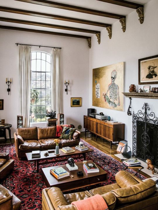 an electic living room with modern furniture balanced with vintage artworks and boho chic rugs
