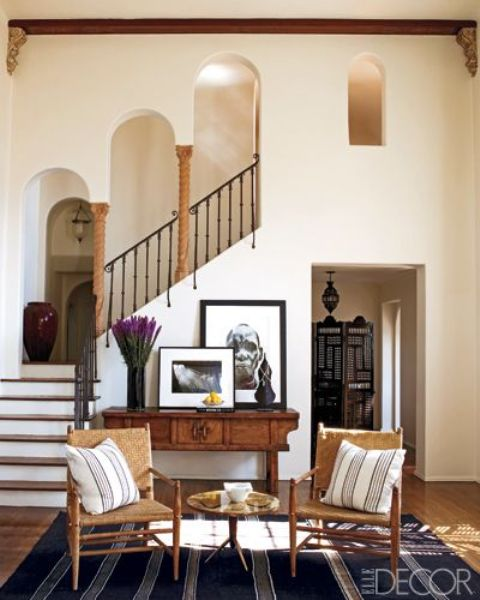 neutral textural walls, wrought railings, little pillars and wooden furniture make up a cool MEditerranean space