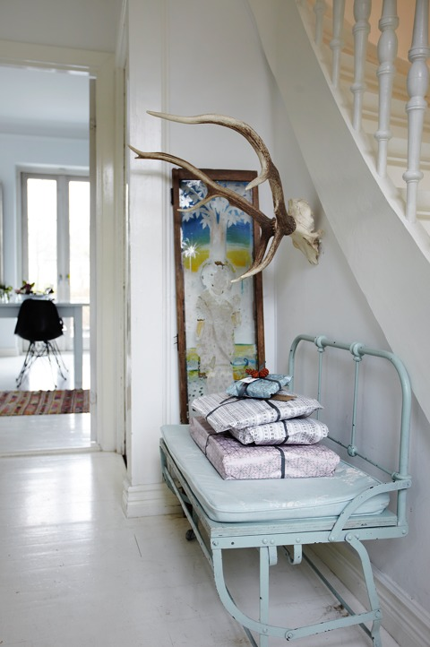 The entryway features a light blue beanch with a stack of gifts and antlers to use as a coat rack