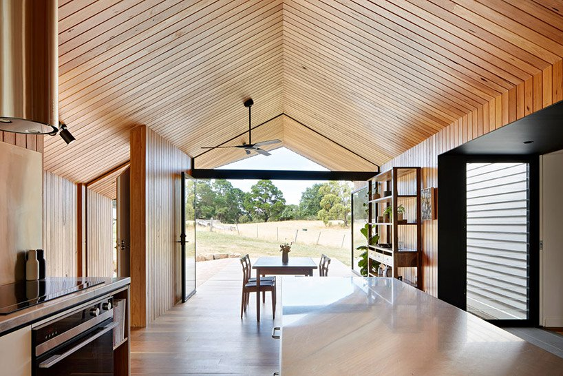 The kitchen is united with a dining space, the whole space is opened up to outdoors with glass doors