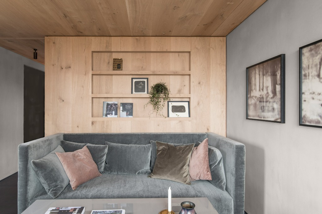 The living room features a grey sofa, some incorporated shelves and artworks