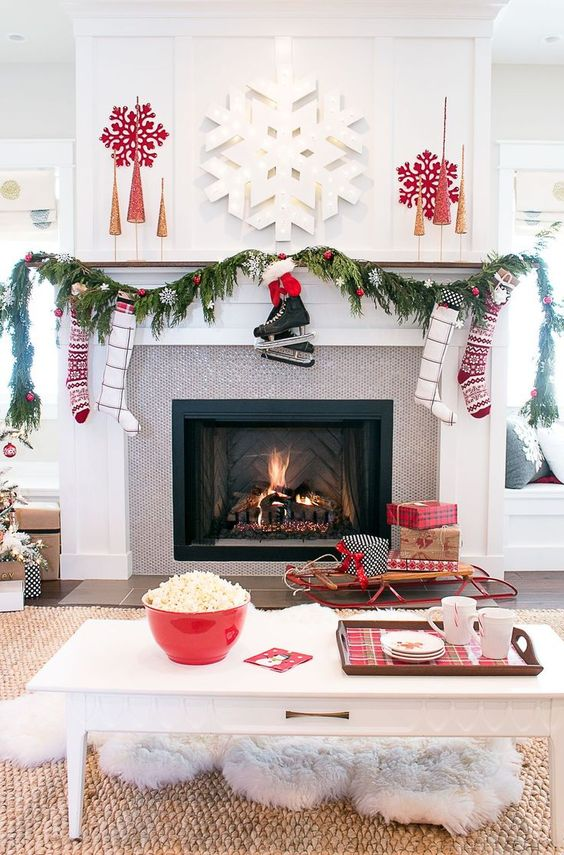 a beautiful contemporary living room dotted with reds, snowflakes, gifts, stockings and red ornaments