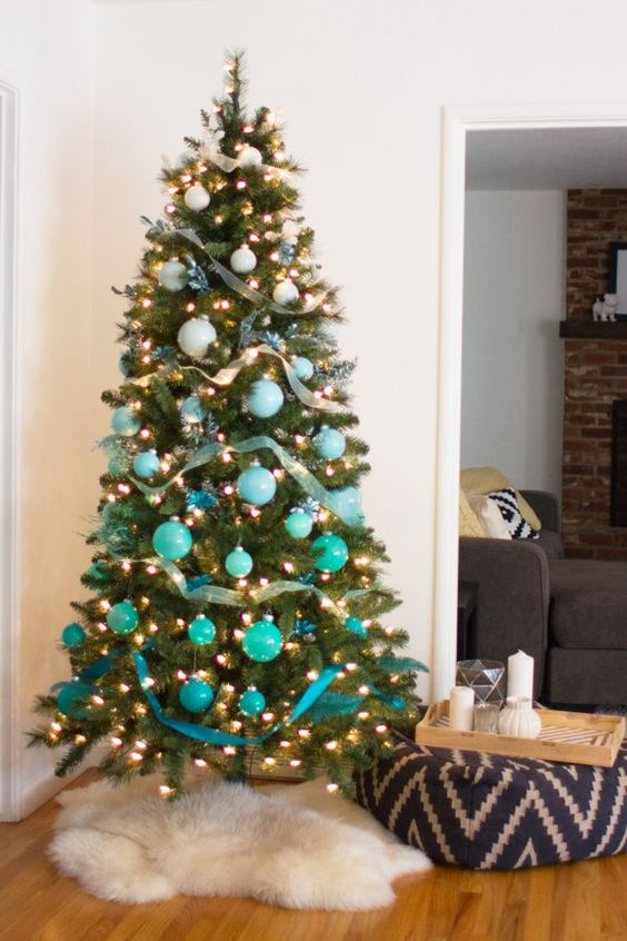 a bold ombre Christmas tree from white to turquoise and blue with lights and ribbons is ideal for a beach Christmas