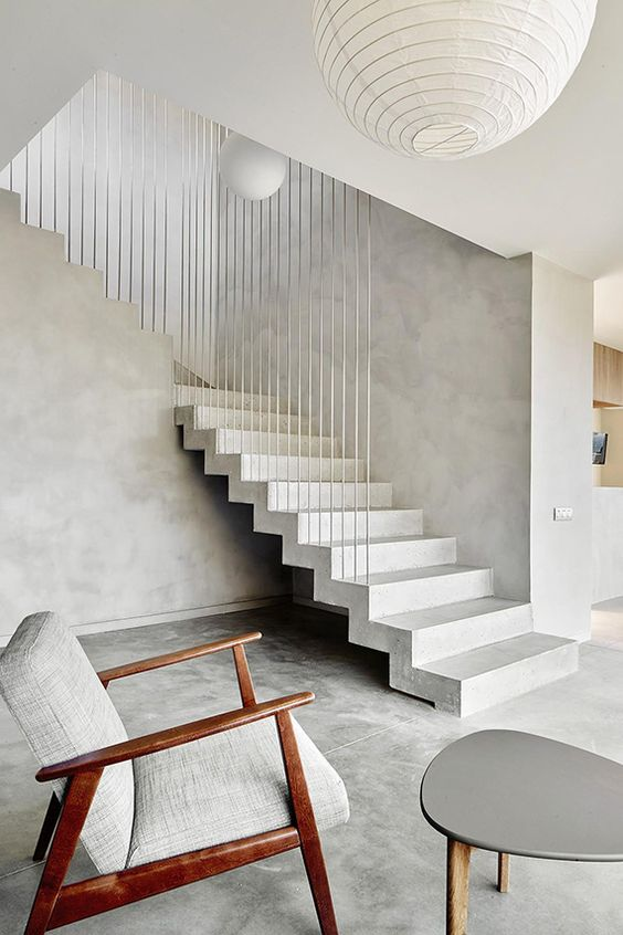 a minimalist entryway with a concrete staircase and timelessly elegant furniture