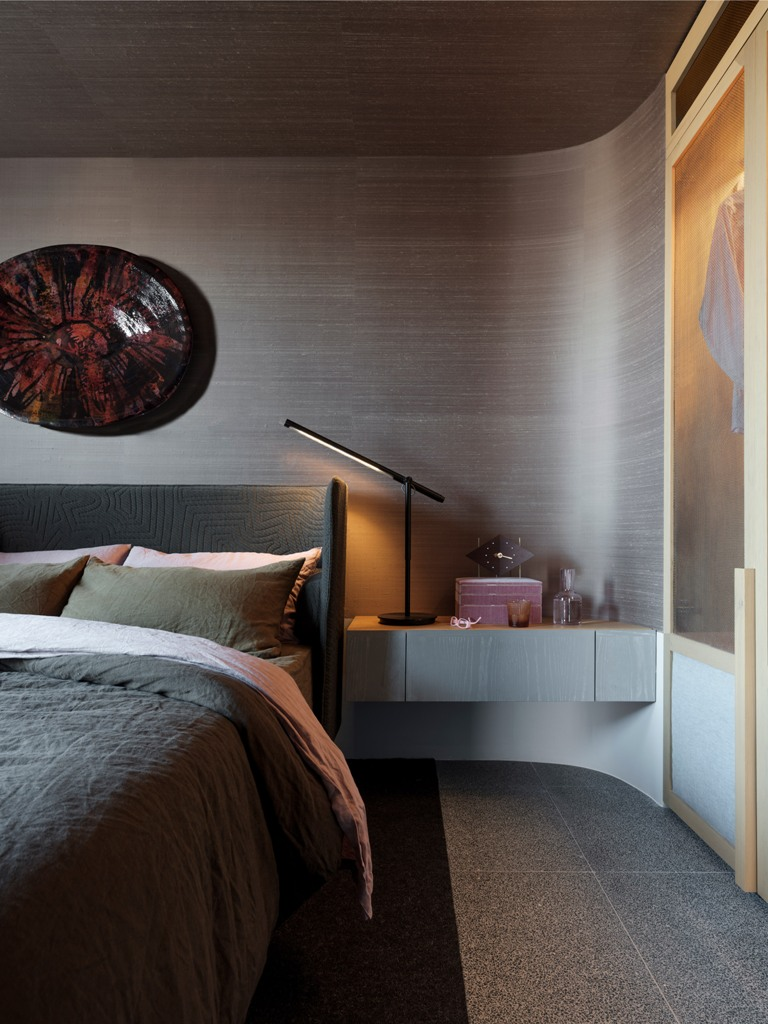The bedroom features a beautiful rounded wall, an upholstered bed, artworks and floating bedside tables