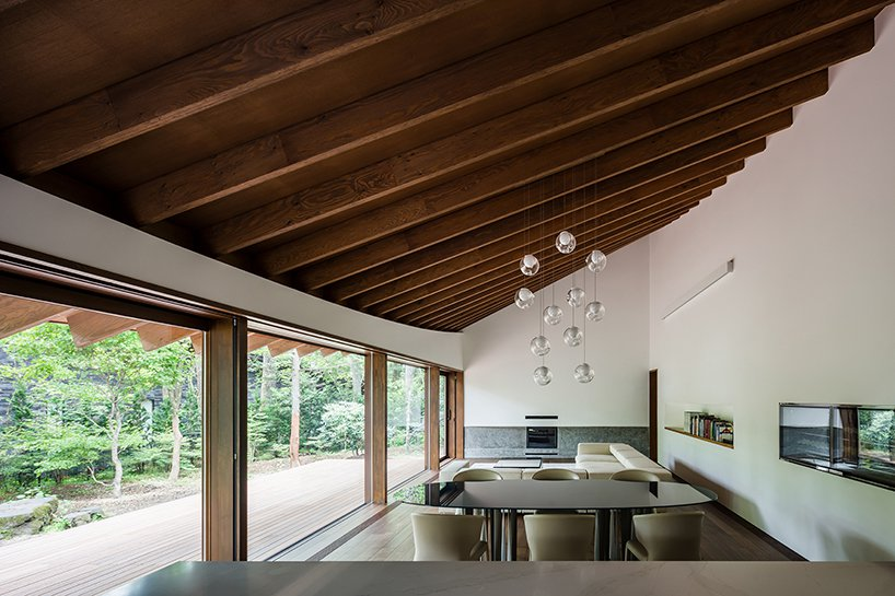 The main space is a living and dining one, with an attic roof accented with pendant glass bubble lamps and cool forest views