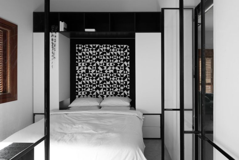 The master bedroom features a bold geometric headboard, a large bed and enough storage space