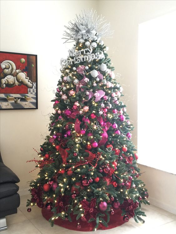 a bold ombre silver to pink and red Christmas tree with lights, fabric flowers and bows plus a creative topper