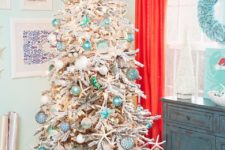 06 a flocked Christmas tree with float-like ornaments, lights, star fish features strong coastal vibes