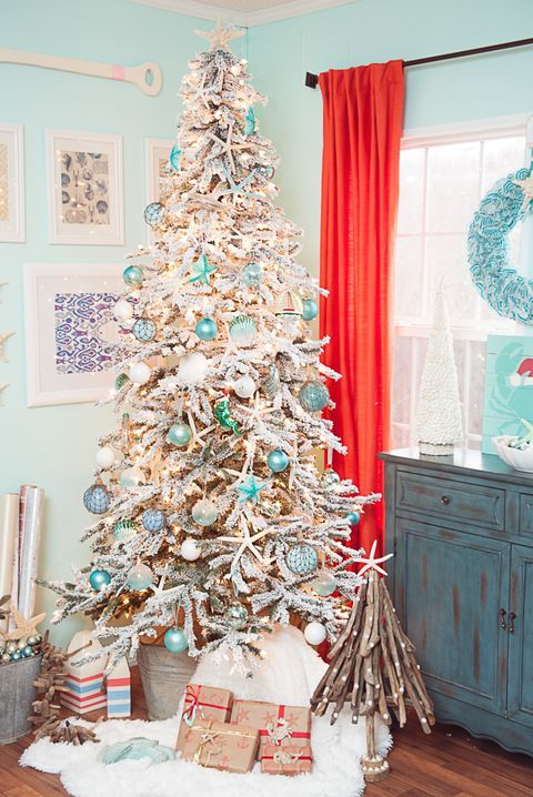 a flocked Christmas tree with float like ornaments, lights, star fish features strong coastal vibes