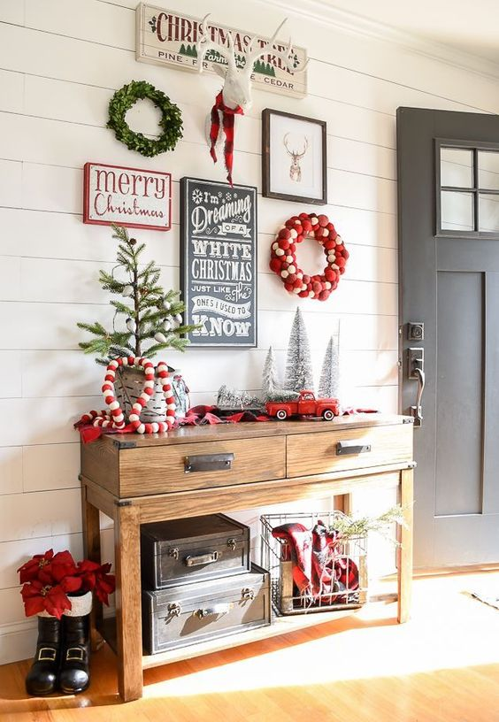 a gorgeous gallery wall for holidays with a couple of wreaths, signs and a fake deer head for your entryway